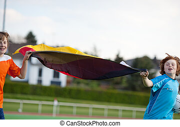 two boys running on soccer field with german flag