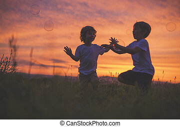boys running to hit bubble on a sunset meadow - Two boys...