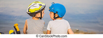 Two boys sit on the shore of the lake after riding a bike and scooter BANNER, LONG FORMAT