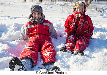 Two boys sitting at the snow on park