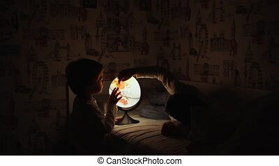Two boys sitting in bed at night rotating the globe and dreams of traveling.