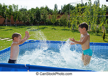 Two boys splashing - Two excited boys splashing in swimming...