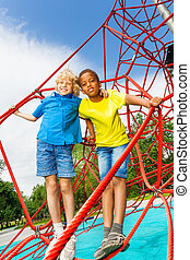 Two boys stand hugging on red ropes of net