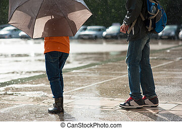 Two boys stand in the rain