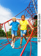 Two boys stand together on red ropes of net