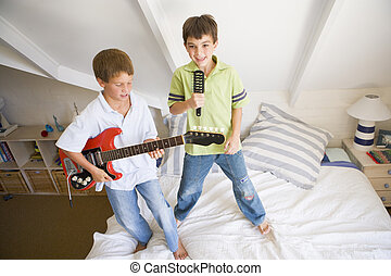 Two Boys Standing On A Bed, Playing Guitar And Singing Into...