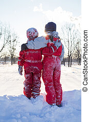 Two boys standing togerher at the snow on park