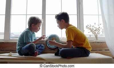 Two boys studying the geography of the earth with a globe.