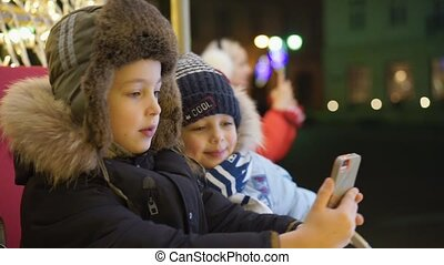 Two boys take selfie on the square near the Christmas tree