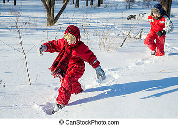 Two boys walking at the snow on park