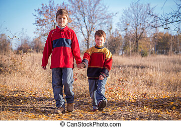 Two boys walking on autumn park
