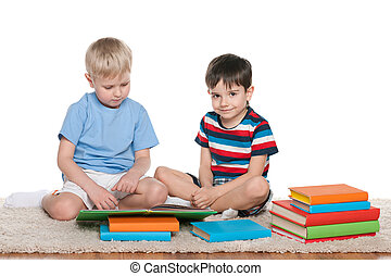 Two boys with books on the floor