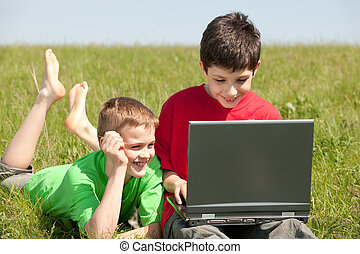 Two boys with laptop on the grass