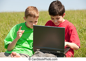 Two boys with laptop on the meadow