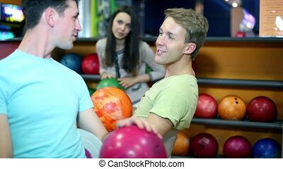 two boys with one girl talk and smile at bowling club -...