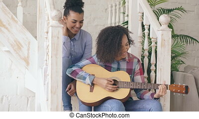 Two brazilian curly girls sistres sitting on stairs and...