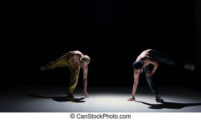Two breakdance dancers with naked torso continue dance, on black, shadow