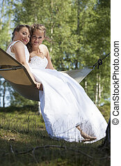 two brides romantically involved in hammock against blue sky with forest background