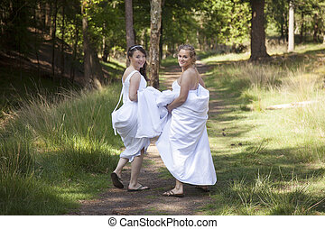 two brides walk on forest path with skirts in their arms while looking back smiling