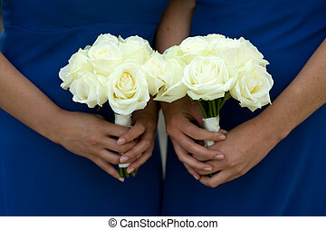 two bridesmaids holding white rose wedding bouquets