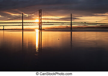 Two bridges against the setting sun and the sea