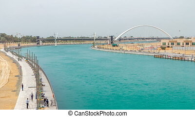 Two bridges over newly opened Dubai canal with a boat crossing under them timelapse.