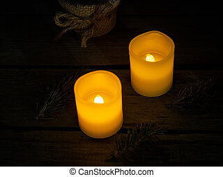 Two bright candles in the dark on a wooden background.