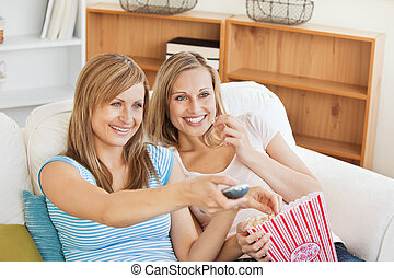 Two bright female friends watching televison on the sofa ...