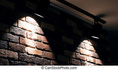 Two bright lamps on a red brick wall indoor