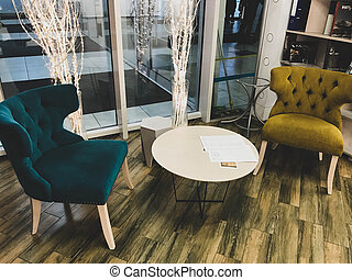 two brightly colored chairs sit next to the coffee table. cozy soft armchairs in green and yellow. cute home furniture. living room furnishings. tea drinking in an armchair at a round table
