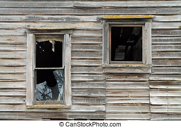 Two Broken Windows in a Dilapidated Brown Wooden House