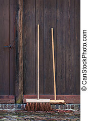 Two brooms in front of an old barn