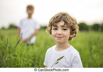two Brother in a green meadow one blur on the back