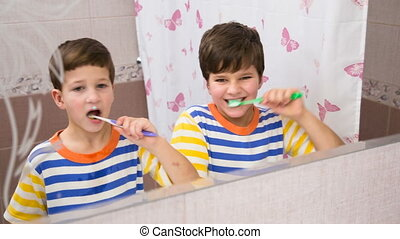 Two brothers cleaning his teeth together in the bathroom...