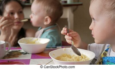 Two brothers eat porridge at home with their mother. They sit at one small table at home and eat with a spoon