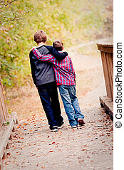 Two brothers hugging and walking on bridge