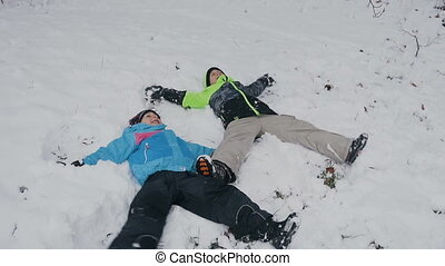 Two brothers in the colored winter clothes lay on the snow in forest and play waving with hands and feet. Winter holiday. December, January