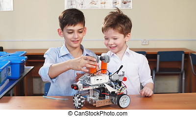 Two brothers kids playing with robot toy at school robotics class, indoor.