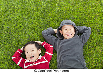 two brothers lying on the meadow in the park