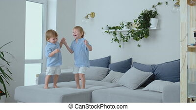 Two brothers of little boys are jumping on the couch and...