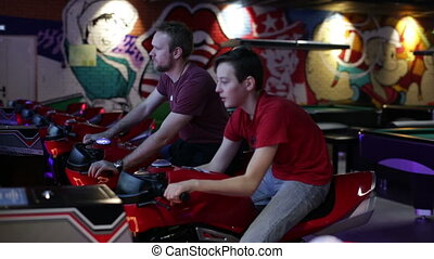Two brothers playing arcade video racing game - Two brothers...