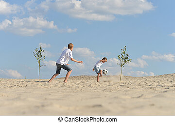 Two brothers playing football on beach in summer day