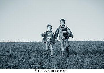 Two brothers running together on green meadow against the sky, v