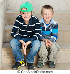 Two brothers - Smiling two brothers sitting on the stairs ...