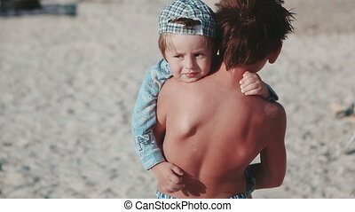 Two brothers. The elder brother holds his younger brother in his arms on the beach. A family.