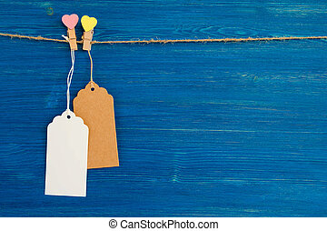 Two brown and white blank paper price tags or labels set and wooden pins decorated on hearts hanging on a rope on the blue wooden background.