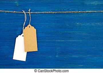 Two brown and white blank paper price tags or labels set hanging on a rope on the blue wooden background.