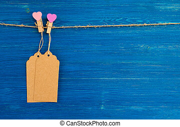 Two brown blank paper price tags or labels set and wooden pins decorated on hearts hanging on a rope on the blue wooden background.