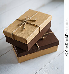 Two brown gift boxes on a wooden white background with a simple bow made of burlap threads.