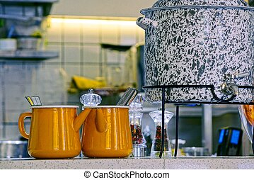 two brown iron mugs and a gray kettle on the table in the kitchen